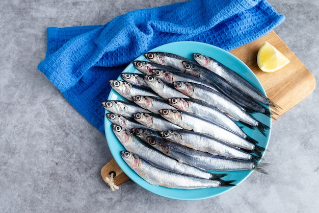 Acciughe intere su piatto blu su fondo marmorizzato