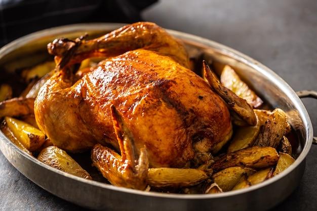 Pollo croccante dorato intero al forno in padella con patate.