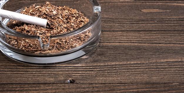 La sigaretta intera e un posacenere di vetro stanno su un vecchio tavolo di legno