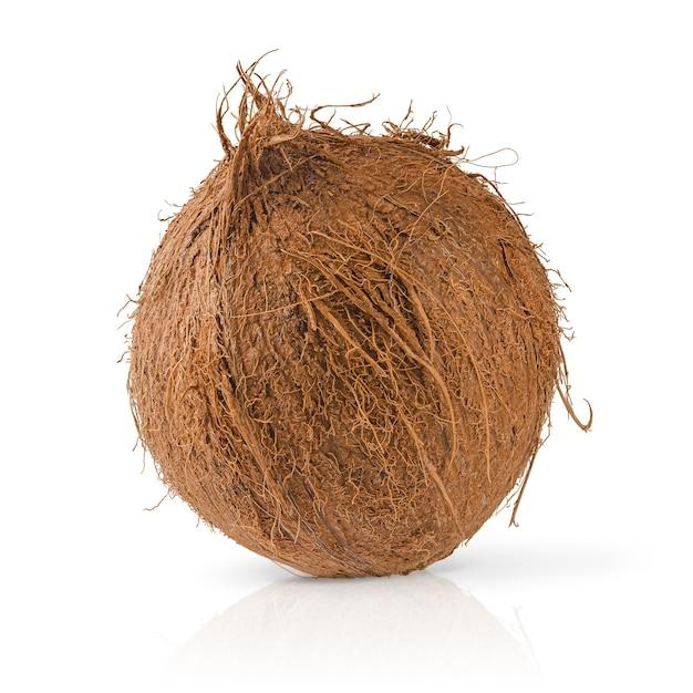 Tutta la noce di cocco isolata sulla superficie bianca con il percorso di residuo della potatura meccanica.