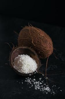 Tutta la noce di cocco con fiocchi di noci di cocco su uno sfondo nero
