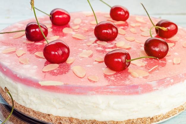 Primo piano intero di cheesecake da dessert con ciliegie, strati di torta