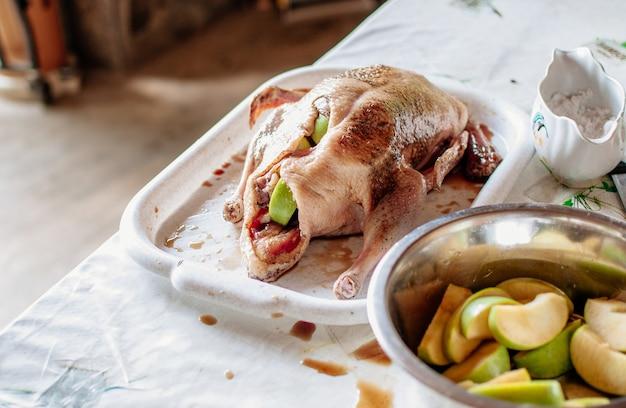 Anatra intera fresca e cruda su un vassoio con ingredienti pronti e spezie. anatra alla pechinese vestita con il concetto di ricetta di riempimento di mele.