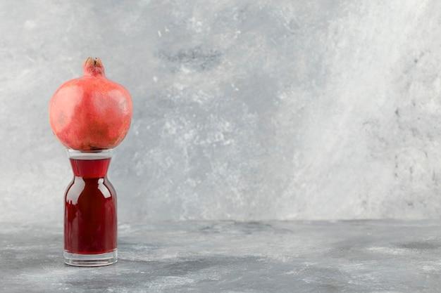 Intero melograno fresco posto sopra un bicchiere di succo di frutta su sfondo marmo.