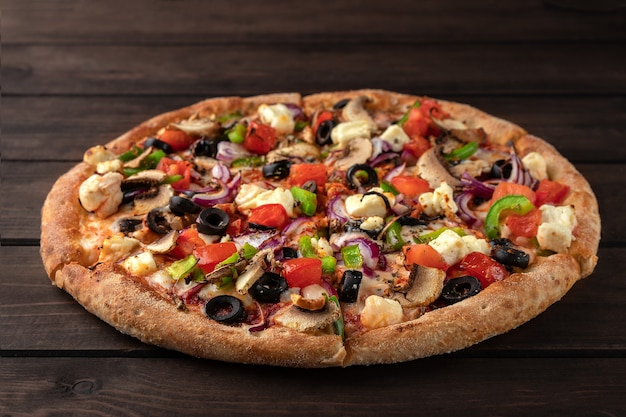 Pizza rotonda fresca intera con il primo piano di carne di pollo, verdure, funghi e formaggio su un tavolo in legno marrone.