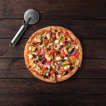 Pizza rotonda fresca intera con carne di pollo, verdure, funghi, formaggio e vista dall'alto di un coltello su un tavolo in legno marrone.