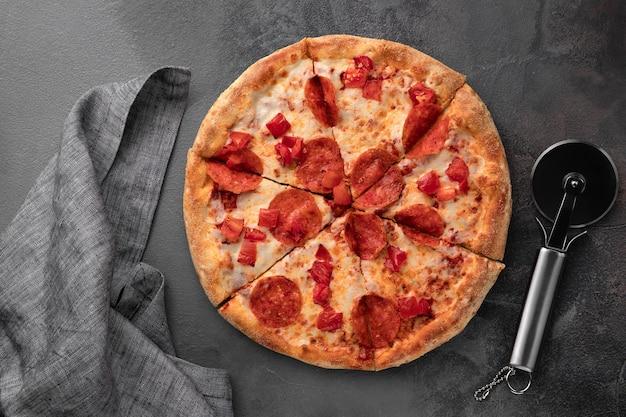 Pizza rotonda fresca intera con salsiccia per pizza e mozzarella e coltello su una vista superiore del tavolo grigio.
