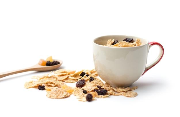 Fiocchi di cereali integrali che hanno mescolato frutti di bosco e uvetta per colazione isolaed su sfondo bianco