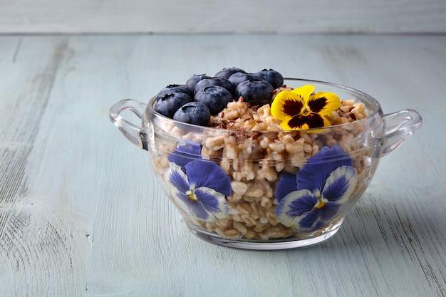 Fiocchi di avena integrale in una ciotola di vetro decorata con fiori mirtilli e semi di lino
