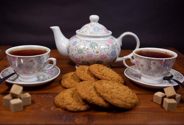 Biscotti di farina d'avena integrale con una tazza di tè e zucchero su un tavolo di legno.