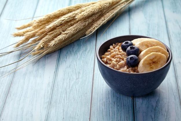 Farina d'avena integrale con mirtilli e banane in una ciotola su un tavolo dipinto di blu nella luce del mattino