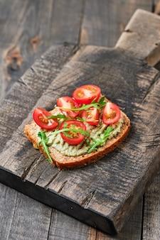 Panini integrali con guacamole, pomodoro e rucola. prima colazione su una tavola di legno.