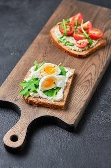 Panini integrali con guacamole, pomodoro, rucola e uova. prima colazione su una tavola di legno.
