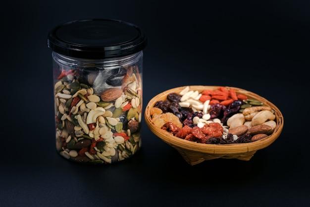 Cereali integrali e frutta secca in un piatto di bambù e una bottiglia di plastica su sfondo nero.