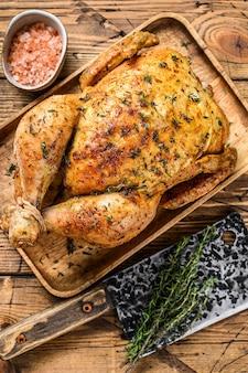 Girarrosto intero di pollo alla griglia. fondo in legno. vista dall'alto.