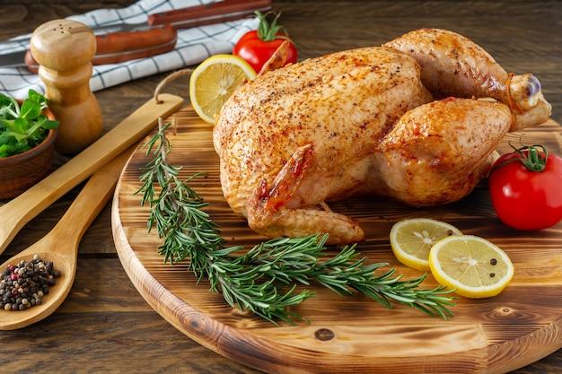 Pollo intero alla griglia con pelle caramellata e rosmarino fresco su un tavolo da pranzo in legno.