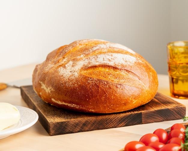 Pagnotta intera di pane di grano bianco appena sfornato sul bordo di legno sul tavolo della cucina domestica