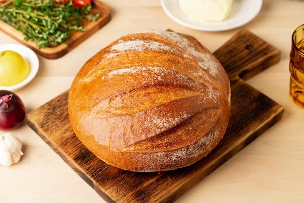 Pagnotta intera di pane di grano bianco appena sfornato sul bordo di legno sulla cucina di casa