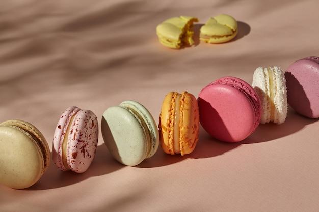 Macarons interi disposti in fila e un biscotto rotto