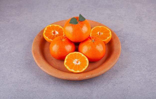 Frutti interi di arancia con foglie verdi poste sulla superficie della pietra.