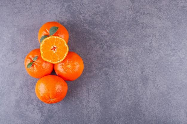 Tutta la frutta arancione con foglie verdi poste sulla piastra bianca.