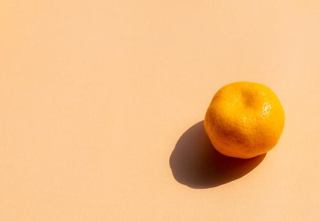 Un intero arance con forte ombra su sfondo arancione, copia spazio