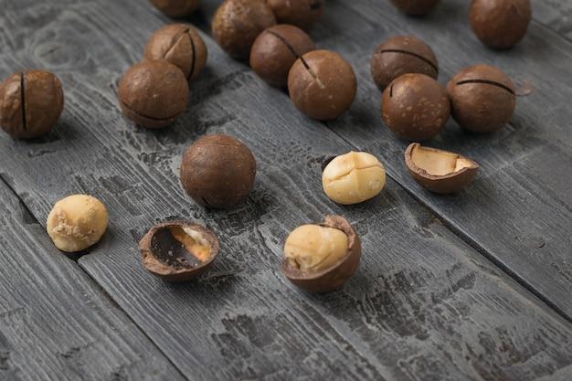 Noci di macadamia intere e sbucciate sparse su un tavolo di legno. superfood.