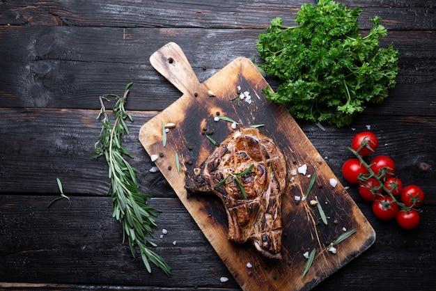 Intero pezzo di carne su un tagliere, bistecca succosa e aromatica, alla griglia, verdure in tavola. posto per il testo.