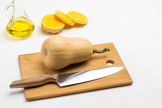 Zucca intera con gambo secco e coltello sul tagliere. pezzi di zucca tritati e olio. vista dall'alto. sfondo bianco