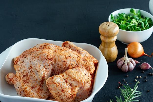 Pollo intero crudo con ingredienti di erbe e spezie in un piatto di ceramica da forno su sfondo scuro pronto da cucinare.