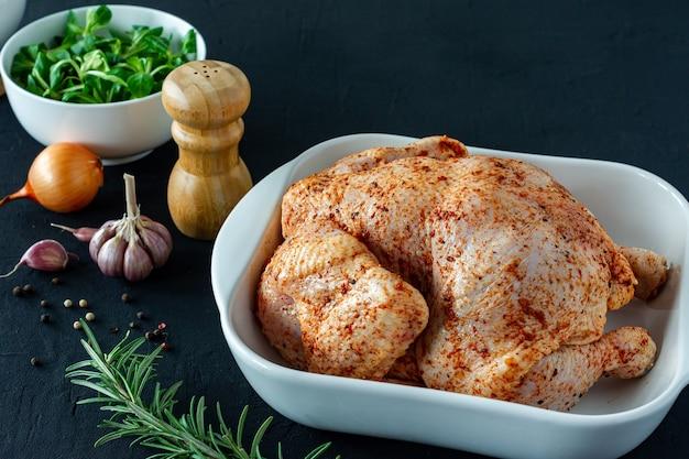 Pollo intero crudo con ingredienti di erbe e spezie su sfondo scuro pronto da cucinare.