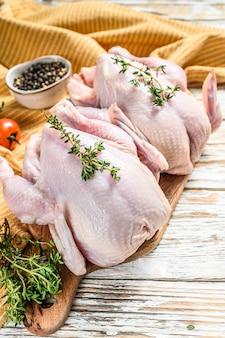 Pollo ruspante crudo intero con timo e spezie. sfondo bianco. vista dall'alto.