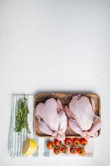 Intero pollo crudo ruspante fresco con erbe e ingredienti, su bianco