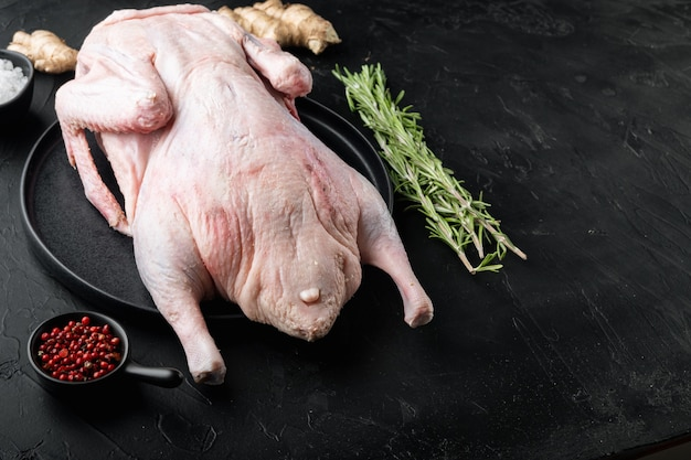 Tutta la carne d'oca cruda sulla tavola nera, con lo spazio della copia.