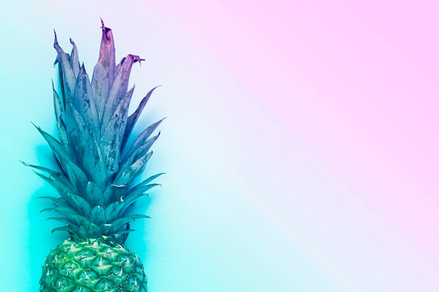 Ananas intero maturo su sfondo blu