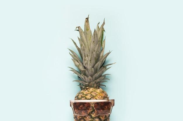 Ananas intero maturo in occhiali da sole su sfondo blu.