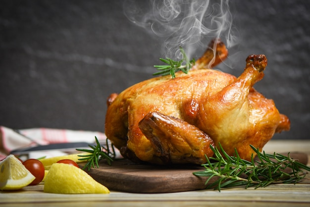 Pollo intero arrosto rosmarino e pomodoro limone sul tagliere di legno - pollo al forno grigliato cibo delizioso barbecue sul tavolo da pranzo in vacanza festeggiare