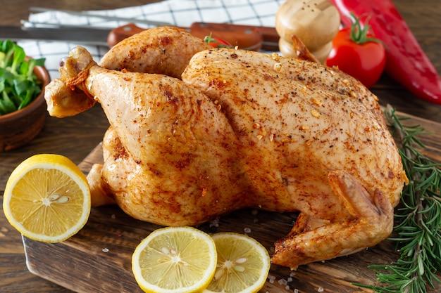 Intero pollo arrosto con limone e verdure sul tagliere. fondo rustico in legno