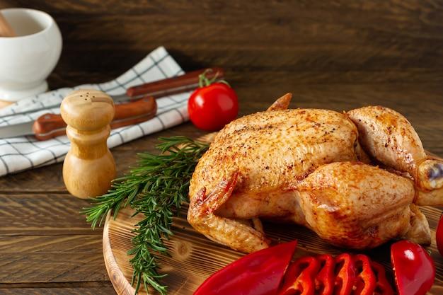 Pollo intero arrosto su un bordo di legno servito con verdure fresche ed erbe aromatiche.