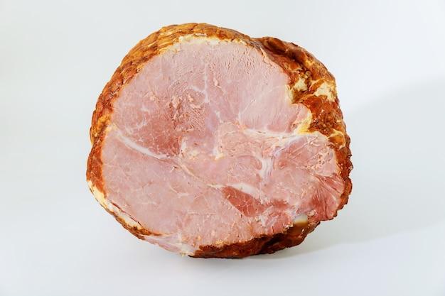 Prosciutto di maiale intero semi disossato isolato su priorità bassa bianca.