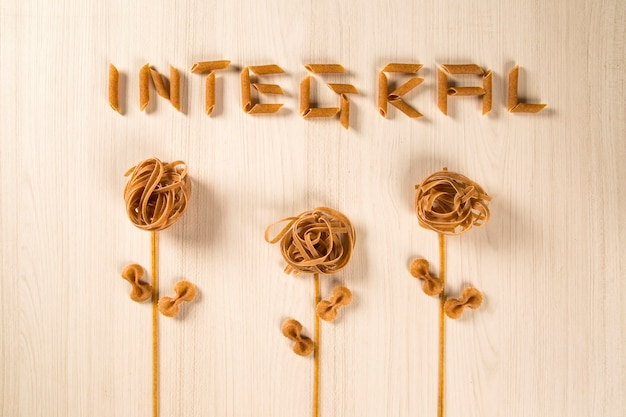 Pasta integrale integrale con fiori su un tavolo di legno bianco
