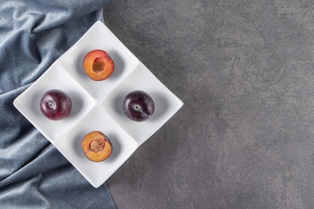 Frutti di prugna rossa succosi interi ed affettati posti su un piatto bianco.