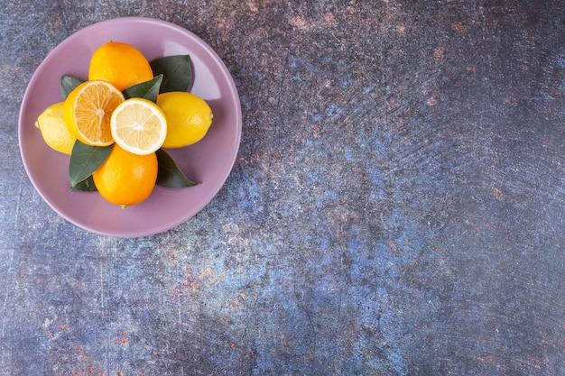 Frutti di limone interi e affettati posti su una pietra.