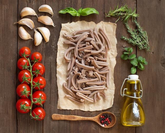 Pasta di farro integrale, verdure, erbe aromatiche e olio d'oliva su superficie di legno
