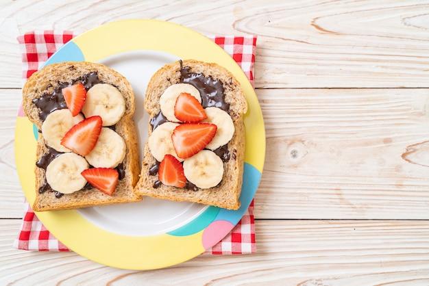 Pane integrale tostato con banana fresca, fragole e cioccolato per colazione