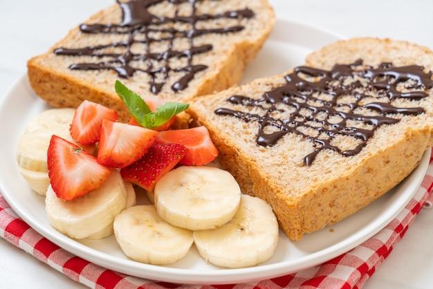 Pane integrale tostato con banana fresca, fragola e cioccolato per colazione