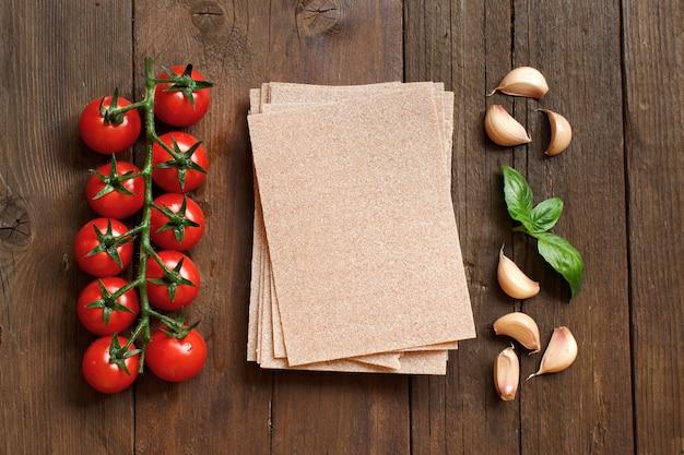 Fogli di lasagne integrali, pomodori, aglio e basilico su una superficie di legno