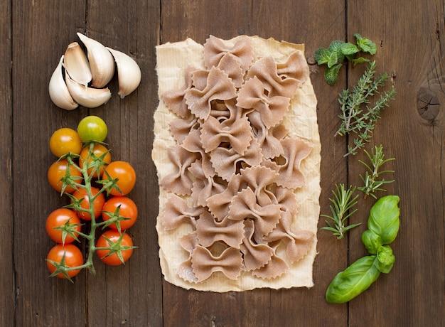 Pasta integrale, verdure ed erbe aromatiche sulla tavola di legno