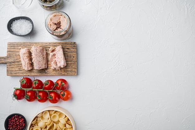 Pasta integrale con pomodori secchi e ingredienti di tonno su bianco, vista dall'alto