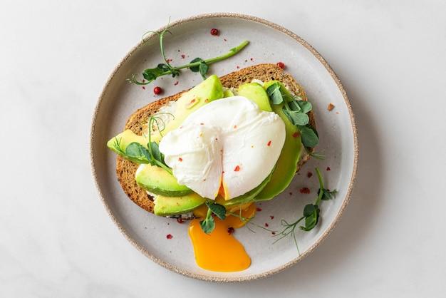 Pane integrale tostato con avocado, uovo in camicia, germogli di piselli e formaggio su bianco